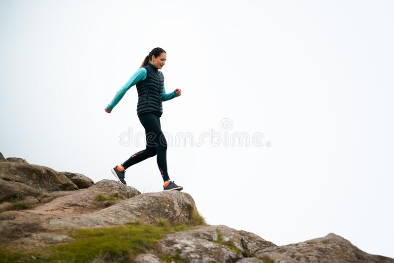 Beautiful Smiling Woman Running on the Mountain Trail at Cold Autumn Evening. Sport and Active Lifestyle royalty free stock photos