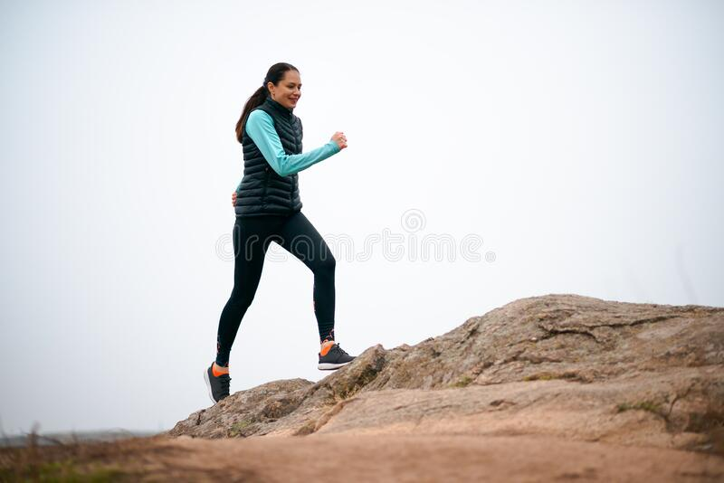 Beautiful Smiling Woman Running on the Mountain Trail at Cold Autumn Evening. Sport and Active Lifestyle royalty free stock images