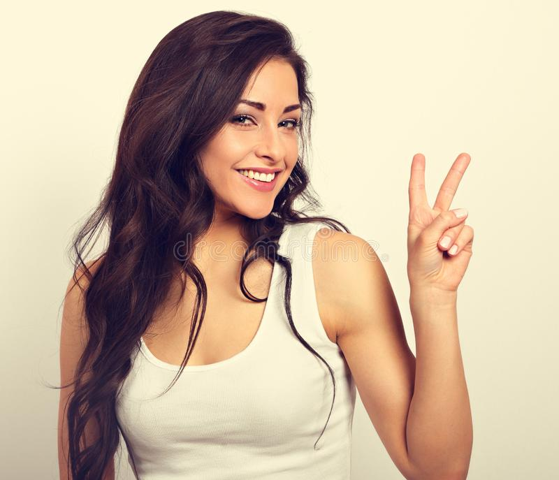 Beautiful smiling woman showing two fingers victory sign in casual clothing. Vintage toned portrait stock photo