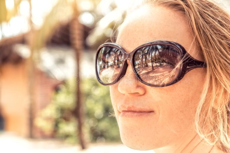 Beautiful smiling woman sunglasses portrait on beach with sunlight on woman face and reflection of beach palm trees in sunglasses stock image