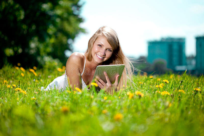 Beautiful smiling woman with tablet pc, outdoors. Beautiful young girl lying on the grass in the field. Smiling trendy stylish. Portrait of young beautiful royalty free stock images