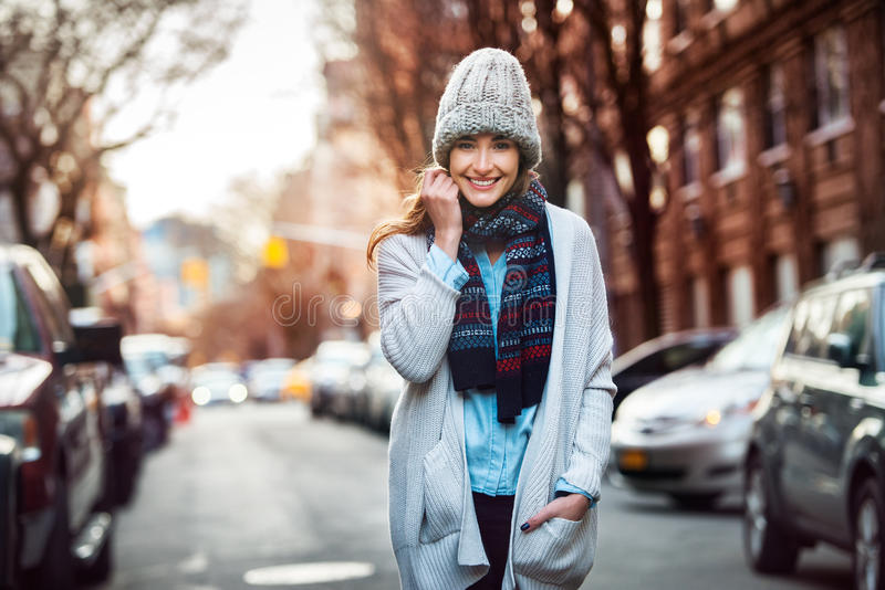 Beautiful smiling woman walking on city street wearing casual style clothes.  stock photography