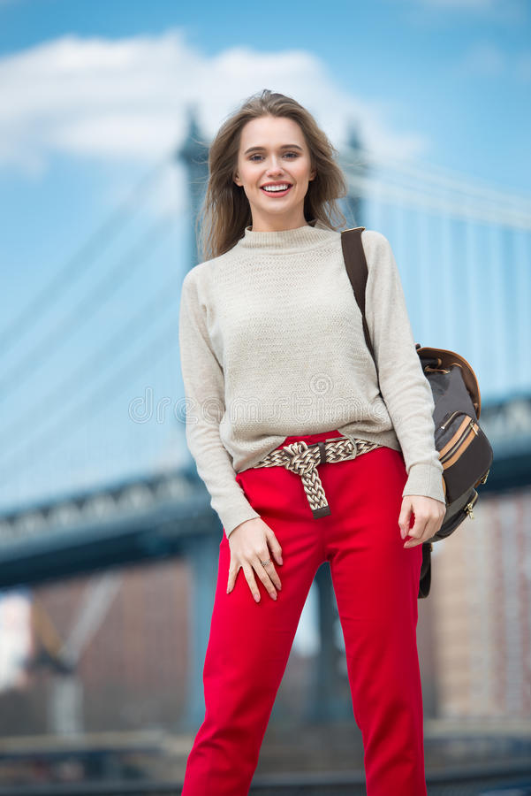 Beautiful smiling woman walking on sunny day in the city royalty free stock photo