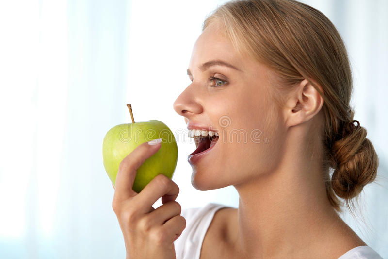 Beautiful Smiling Woman With White Teeth Eating Green Apple stock image
