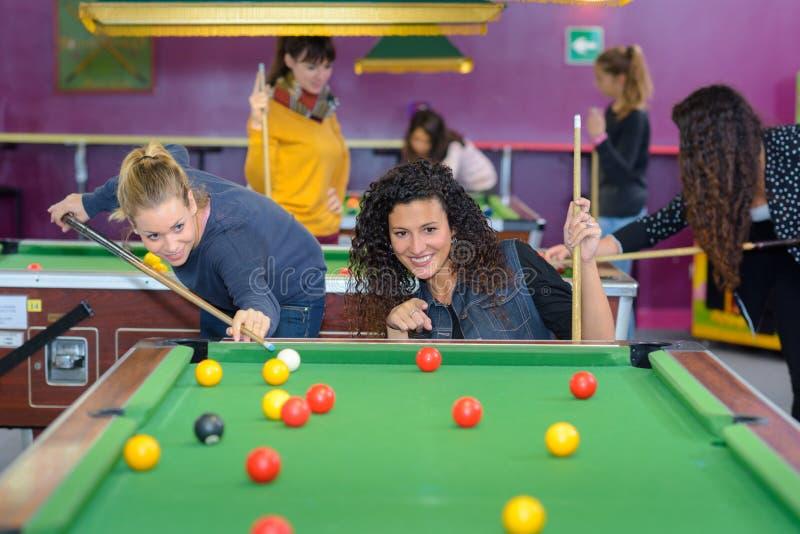 Beautiful smiling women playing billiards at bar royalty free stock image