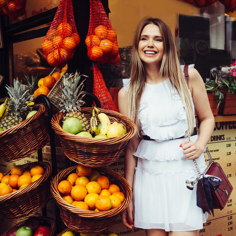 Beautiful smiling young adult woman standing near street fruit store with tropical fruits in baskets. stock photography