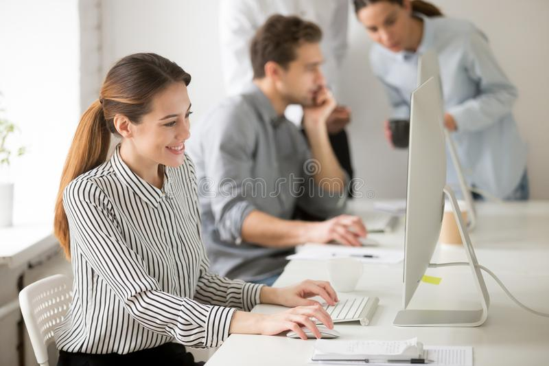 Beautiful smiling young businesswoman working on desktop compute stock photo