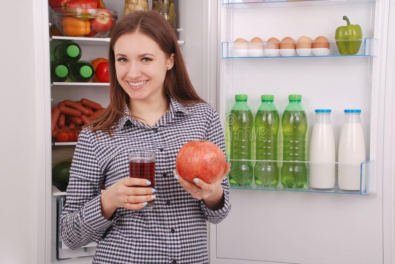 Beautiful smiling young girl holds a glass of pomegranate juice and garnet stock photography