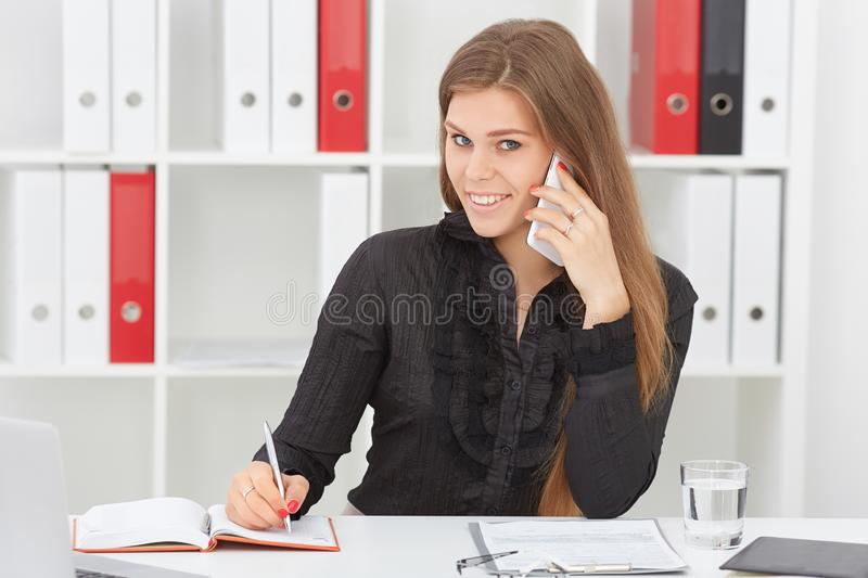 Beautiful smiling young girl make notes talking on the mobile phone sitting at office. royalty free stock photography