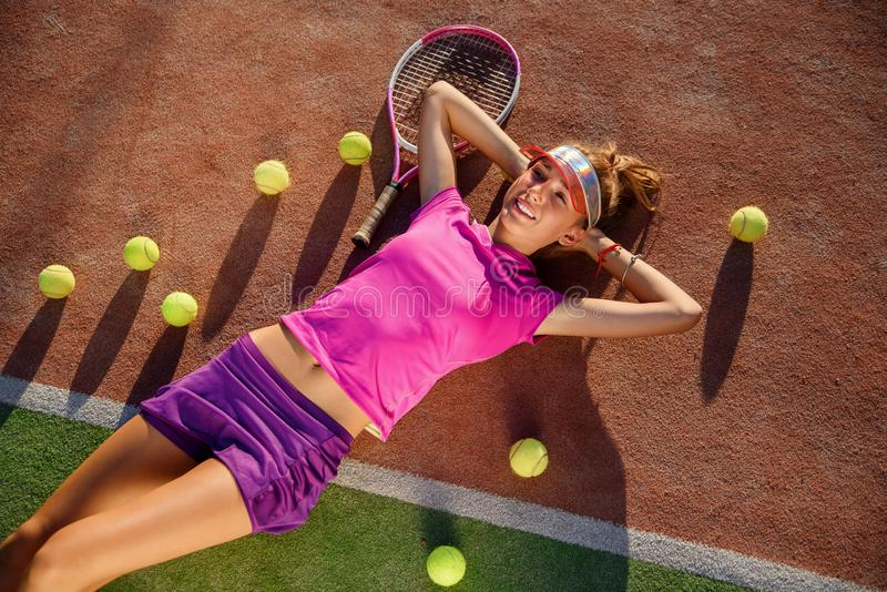 Beautiful smiling young girl in pink uniform and sporty cap lies on outdoor tennis court with a lot of balls after royalty free stock photo