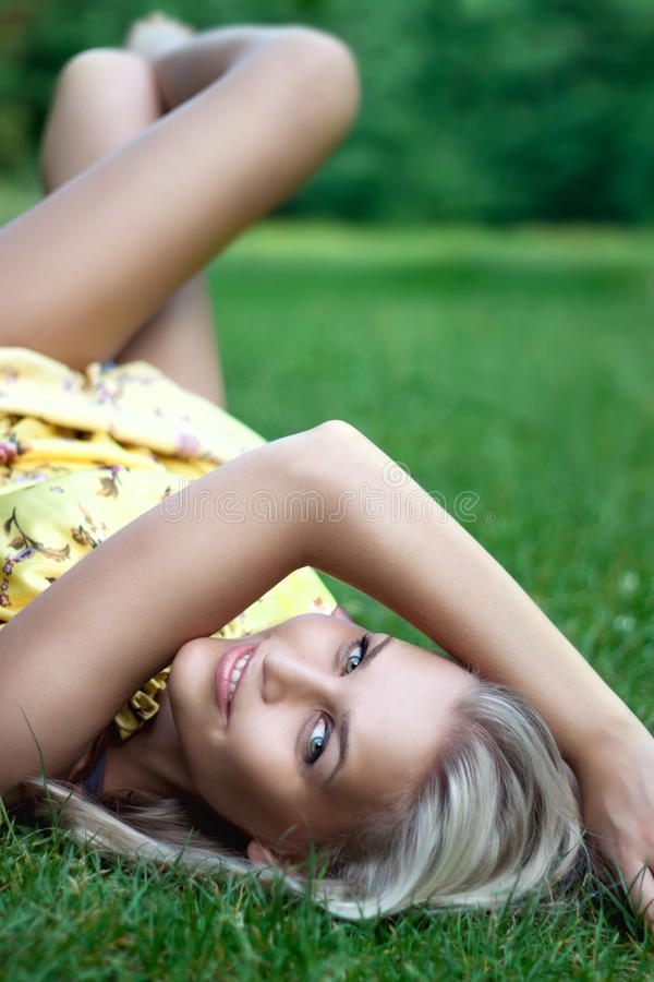 Beautiful smiling young lady laying on the grass royalty free stock images