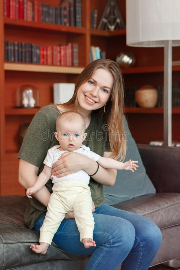 Beautiful smiling young white Caucasian woman mother holding cute adorable baby boy girl child royalty free stock image