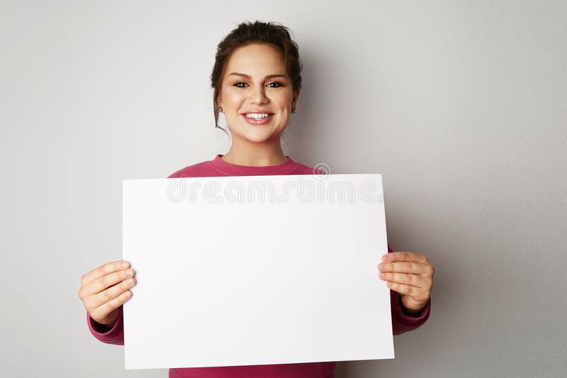 Beautiful smiling young women with banner sign with white blank empty paper billboard with copy space for text over gray royalty free stock photo