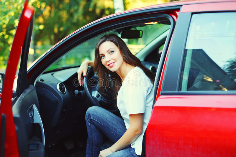 Beautiful smiling young woman driver behind wheel red car. Beautiful smiling young woman driver behind the wheel red car stock photos