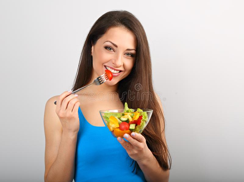 Beautiful smiling young woman eating healthy organic vegetable salad. On blue background with empty copy space royalty free stock photo