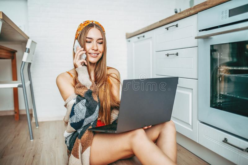 Beautiful smiling young woman fair long hair girl wearing in the  cozy knitted cardigan using mobile and working on laptop at royalty free stock photos