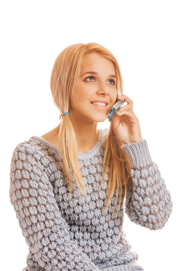 Beautiful smiling young woman in gray sweater talking on a mobil stock photos