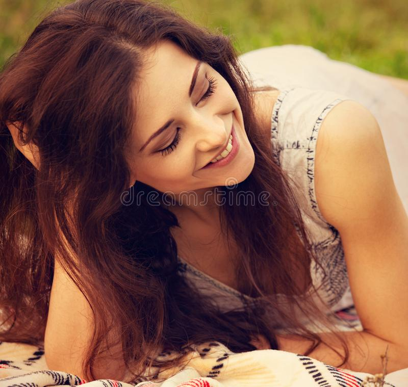 Beautiful smiling young woman with long hair lying on the grass on summer green background. Closeup royalty free stock photography