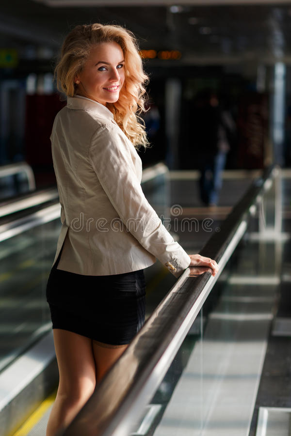 Beautiful smiling young woman looking back while standing on travelator stock photos