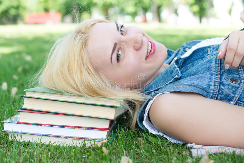 Beautiful smiling young woman lying on grass. And reading blue book, summer green park. Female student girl outside in park. Happy young university student of stock image