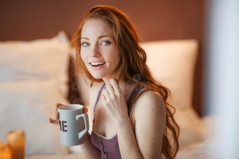 Beautiful smiling young woman with natural make up and long eyelashes holds a cup with hot coffee or tea. Winter season. stock images