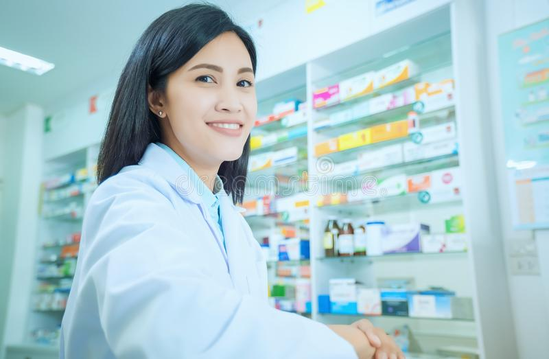 Beautiful smiling young woman pharmacist doing his work in pharmacy. Ok royalty free stock images