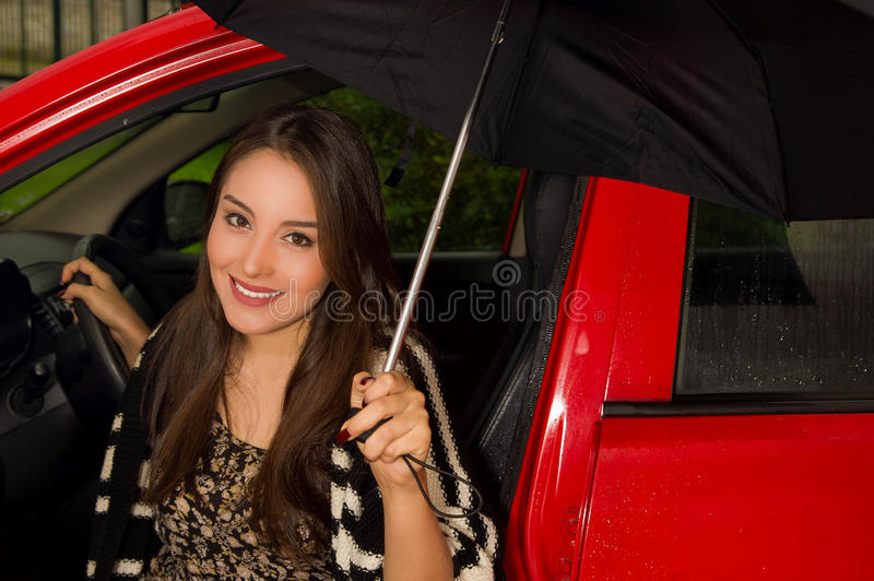 Beautiful smiling young woman in red car wearing a wool jacket and posing for camera and holding an umbrella.  stock photos