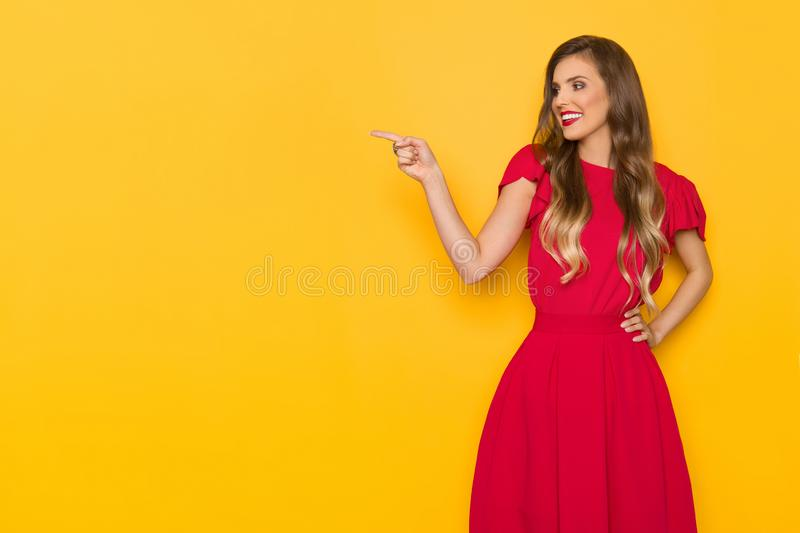 Beautiful Smiling Young Woman In Red Dress Is Pointing And Looking Away royalty free stock images