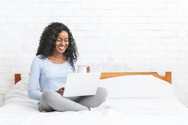 Beautiful smiling young woman sitting on bed, using laptop stock image