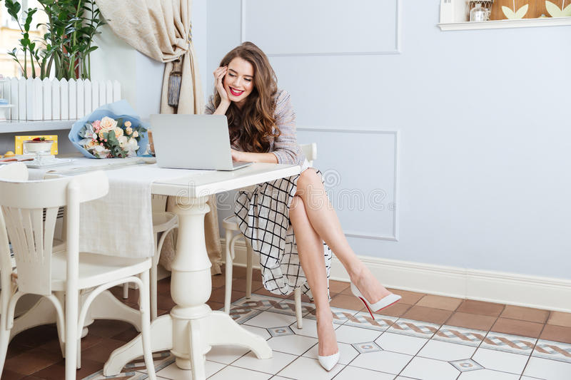 Beautiful smiling young woman sitting and using laptop in cafe stock photos