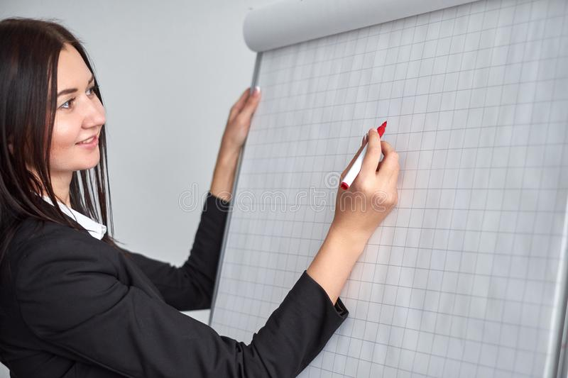 Beautiful smiling young woman writing on a blank flipchart in office as she does a presentation or promotion royalty free stock photos