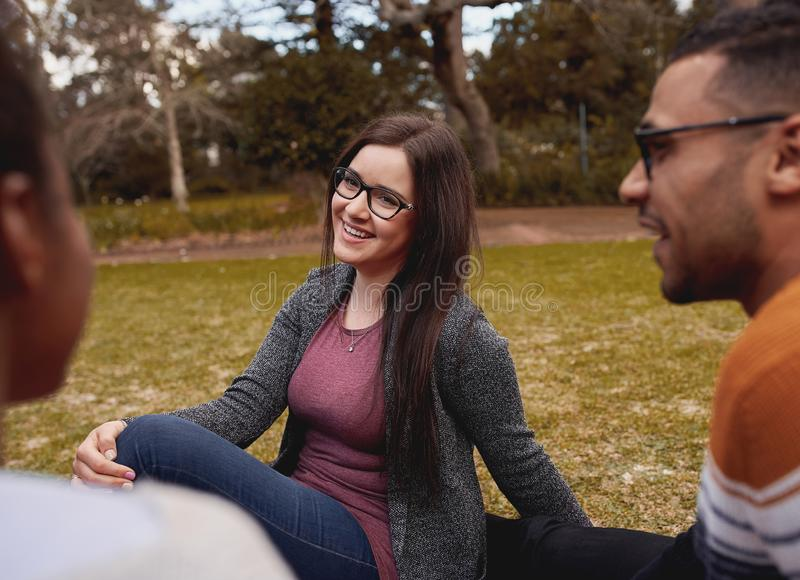Portrait of a beautiful smiling young woman wearing eyeglasses relaxing with her friend in the park stock photos