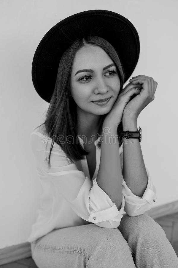 Beautiful smilling young girl in a white shirt and black hat. Black-white photo. stock image