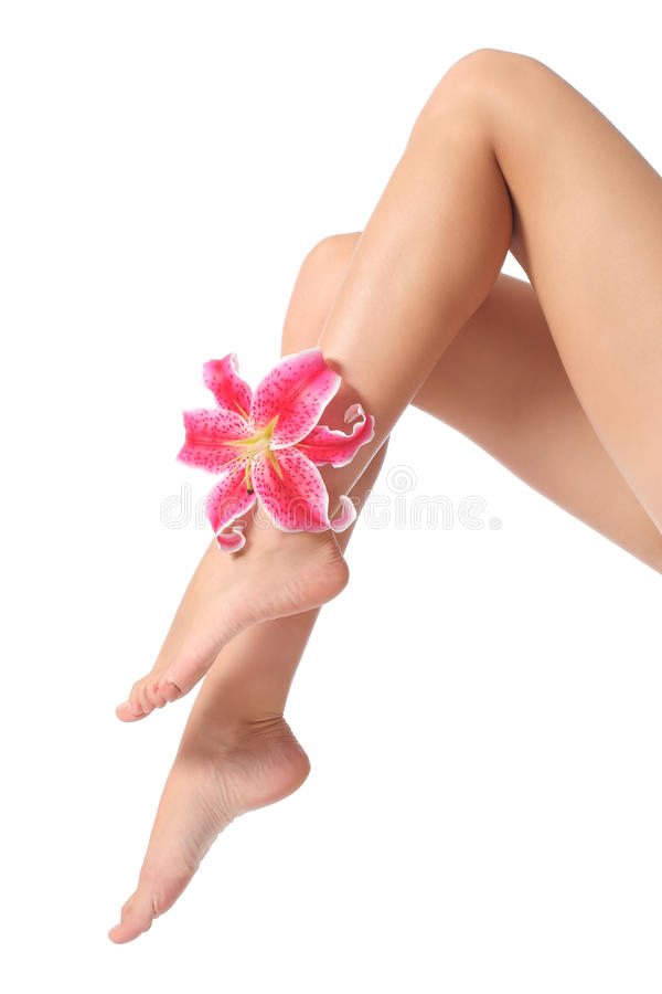 Beautiful smooth and waxed woman legs with a flower stock image