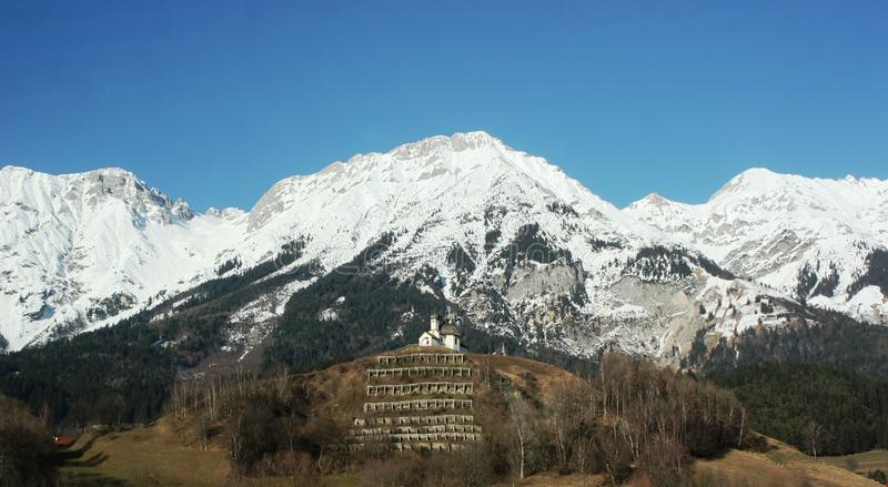 Beautiful snow capped mountain and hill top church royalty free stock photography