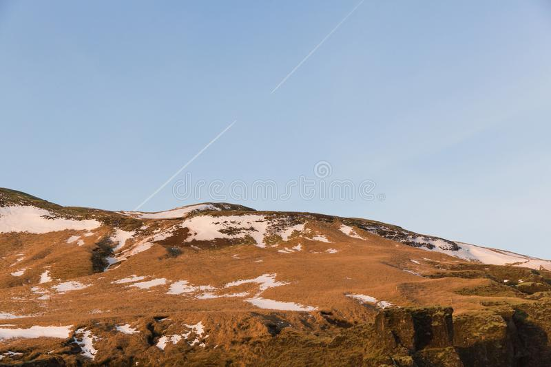 Beautiful snow-covered grassy hills and blue sky. In iceland stock photography