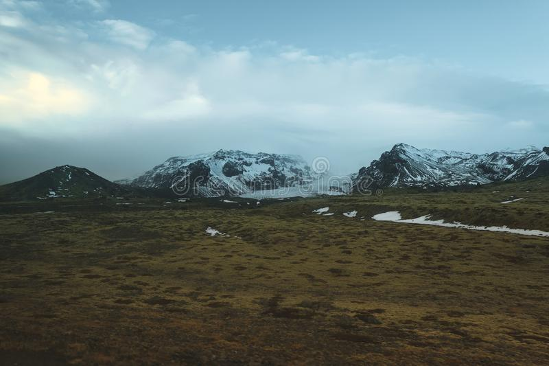 Beautiful snow-covered mountains and green vegetation on meadow. In iceland royalty free stock image