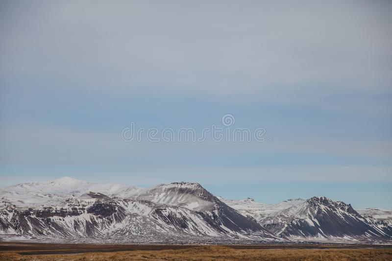 Beautiful snow-covered mountains and plain with dry grass. In iceland, snaefellsnes stock photos
