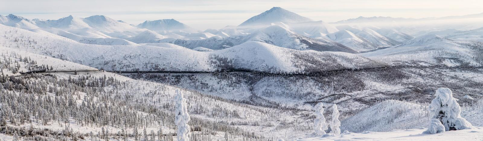 Beautiful snow covered winter road and trees in snow capped mountains, kolyma highway,. Russian federation stock photo