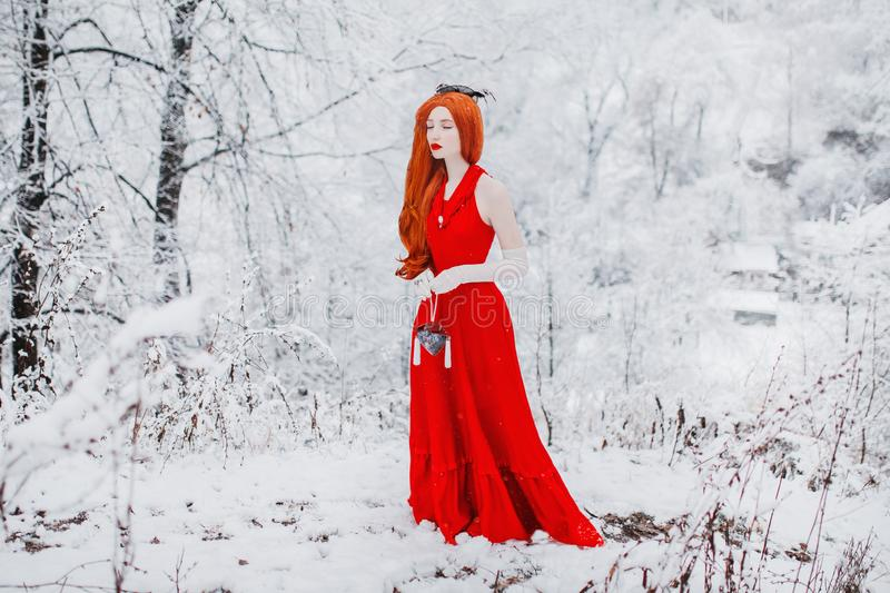 Beautiful snow maiden girl with red hair on february nature. Beautiful redhead retro woman in red gown and with long gloves on bac. Kground of winter nature stock images
