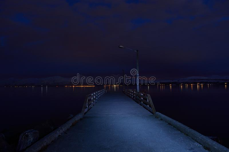 Beautiful snowy mountain and cold blue fjord with pier royalty free stock photo