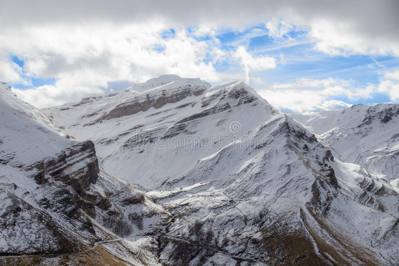 Beautiful snowy mountains and cloudy sky royalty free stock photo