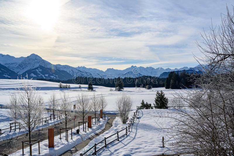 Beautiful snowy winter landscape with loipe and mountains in South Germany. royalty free stock photos