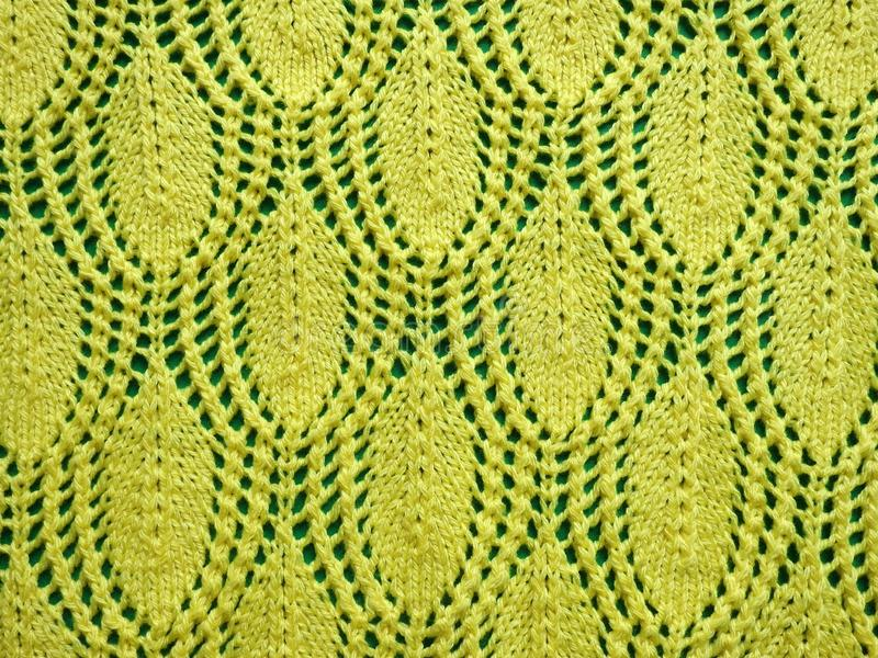Yellow knitted surface texture on green background royalty free stock photography