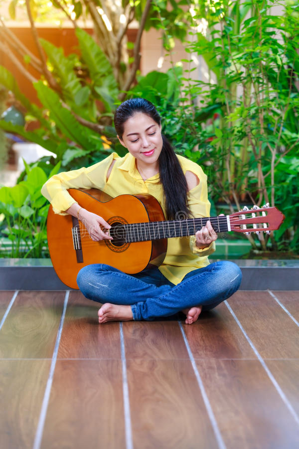 Beautiful songwriter writing on note paper with acoustic guitar royalty free stock image