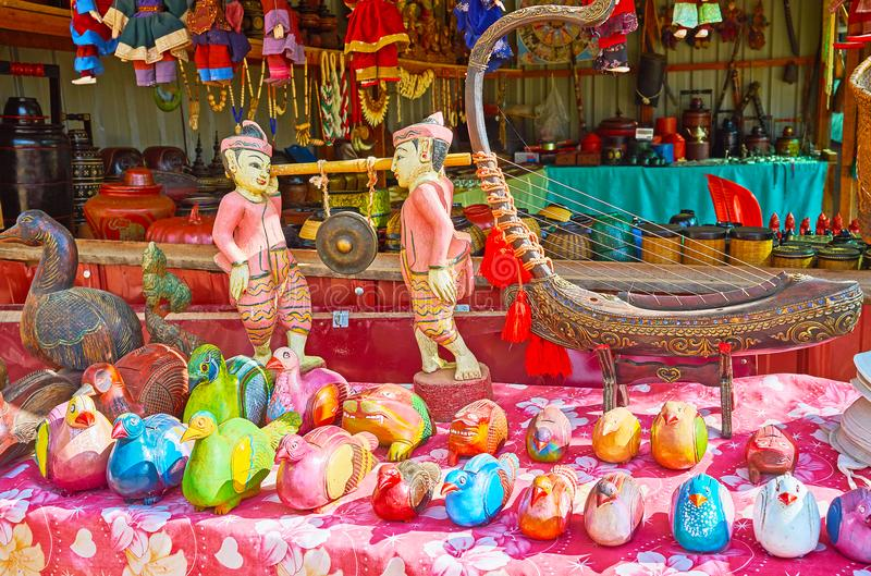 Attractive souvenirs of Burmese tourist market, Inn Thein, Myanmar. The beautiful souvenir gong and traditional musical instrument, named saung-gauk arched harp royalty free stock photography