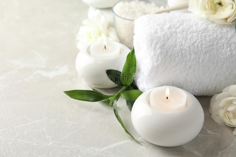 Beautiful spa composition with candles and flowers. On marble background, space for text stock photo