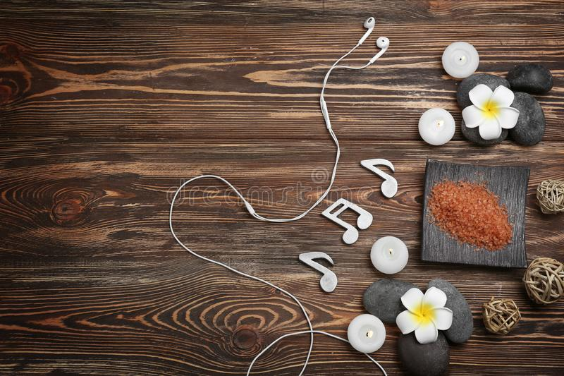 Beautiful spa composition with earphones and music. Notes on wooden background stock image