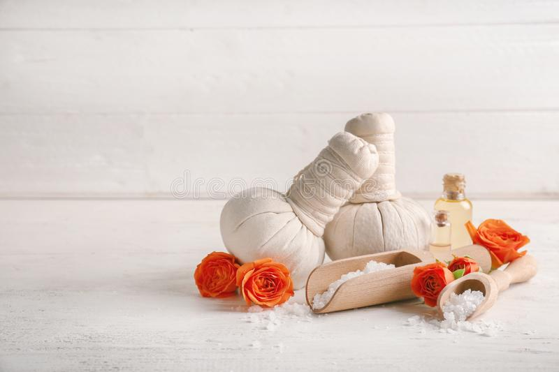 Beautiful spa composition with herbal bags, sea salt and bottles of essential oil on white table stock images