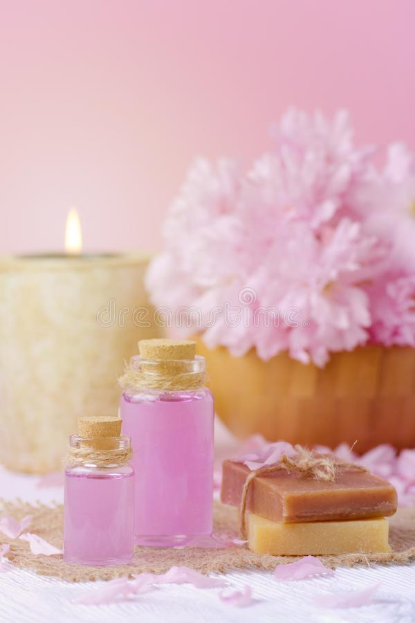 Beautiful spa composition with massage oil, candle, soap bar and fresh pink flowers. Beautiful spa composition with massage oil, soap bar and fresh pink flowers stock photo